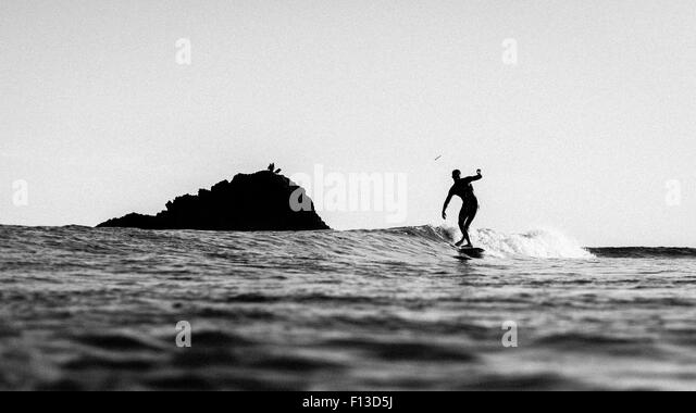 Silhouette of a man surfing - Stock Image
