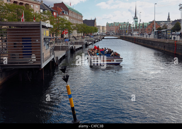 The canal cruise boat 'The Ugly Duckling'  has just taken onboard passengers at  the stop 'Ved Stranden'. - Stock Image