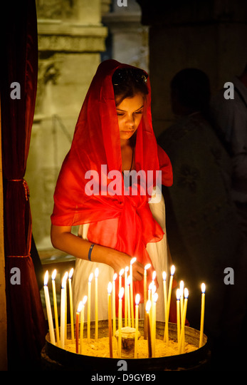 Woman lighting a candle at the church of the Holy Sepulchre in the old city, Jerusalem, Israel. - Stock-Bilder