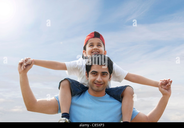 Son getting a piggyback ride from his father - Stock-Bilder