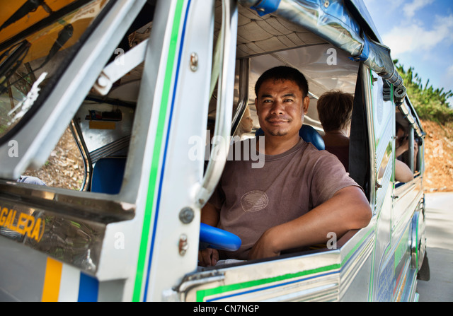 Bus driver smiling at window - Stock Image