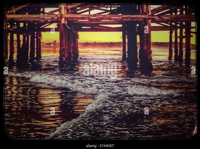 Pacific Ocean waves rolling in under pier at sunset - Stock Image