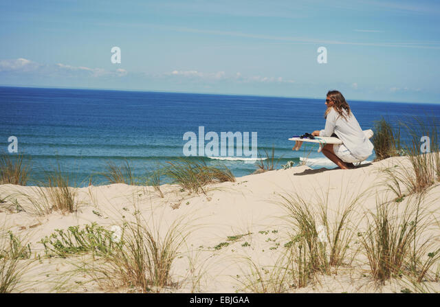 Woman with surfboard on beach, Lacanau, France - Stock Image