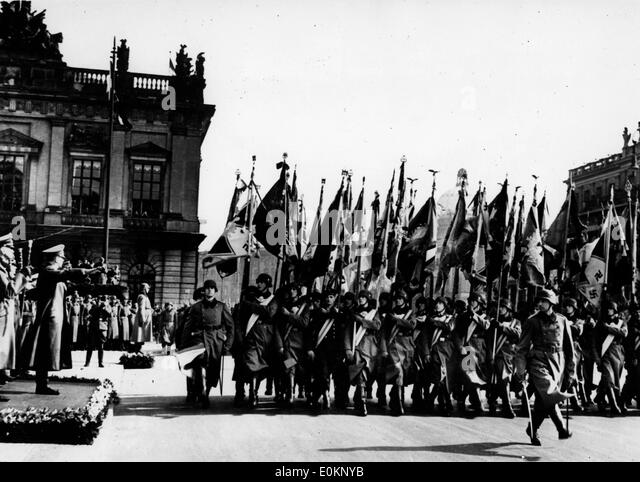 Adolf Hitler takes the salute while soldiers hold their regimental flags - Stock-Bilder