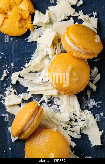 Whole and broken orange lemon homemade macaroons with chopped white chocolate and citrus sugar and zest on dark - Stock Image