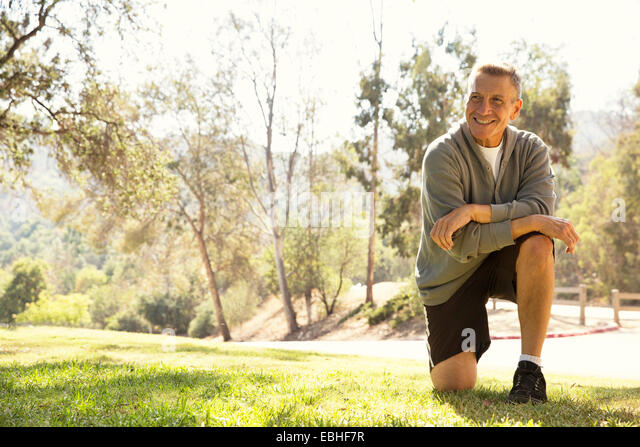 Portrait of mature male runner on one knee in park - Stock Image