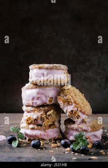 Set of homemade blueberry ice cream sandwiches in oat cookies with almond sugar crumbs, blueberries and mint over - Stock Image
