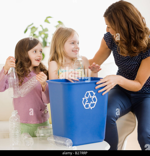 Mother and daughters filling recycling bin - Stock Image