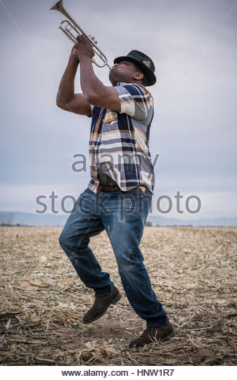 Black man playing trumpet and dancing in field - Stock-Bilder