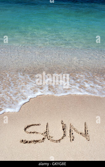 The word Sun written in golden beach sand at the edge of gently lapping surf on a tropical beach conceptual of summer - Stock Image