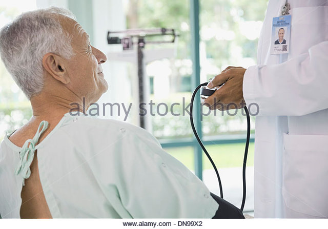 Senior male patient getting blood pressure measured - Stock Image