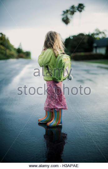 little girl coming home from school on a rainy day, standing in a puddle of water - Stock Image