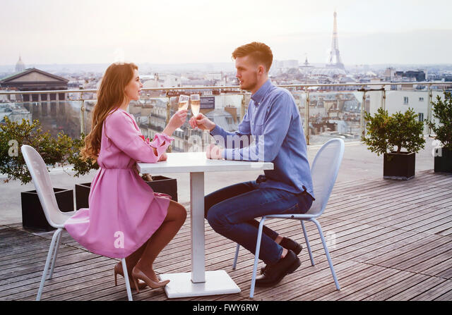 couple drinking champagne in luxury rooftop restaurant in Paris with panoramic view of Eiffel Tower - Stock Image