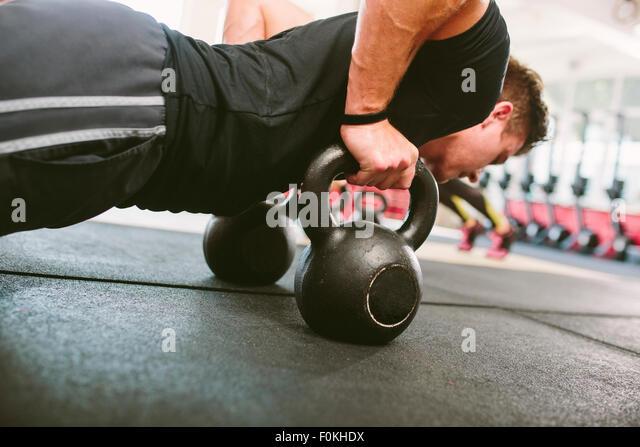 CrossFit athlete doing push-ups on kettlebells - Stock-Bilder