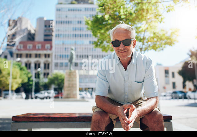 Portrait of handsome senior man sitting outdoors. Mature male tourist with sunglasses sitting outside in the city - Stock Image