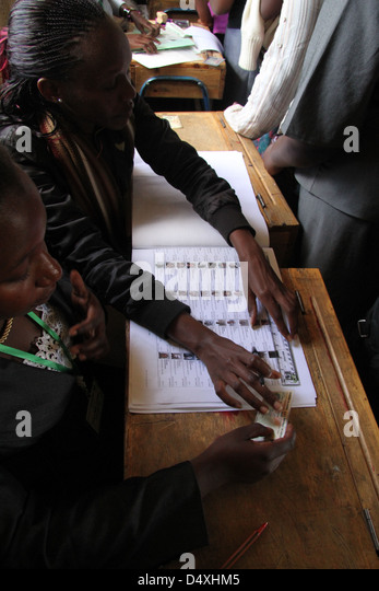 A IEBC cleark checks a voters ID details against the printed register in Makadara Constituency from a printed register. - Stock Image