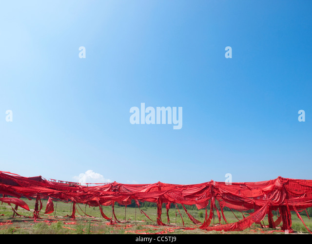 Fence with red prayer flags, Hexigten Global Geopark, Chifeng, Inner Mongolia, China - Stock-Bilder