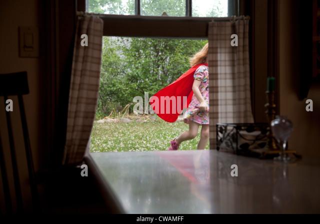Girl in a cape running past an open window - Stock-Bilder