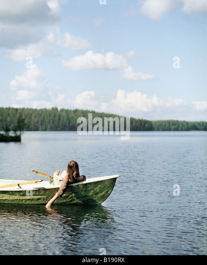 Rear view of a young woman sitting in a rowboat - Stock Image