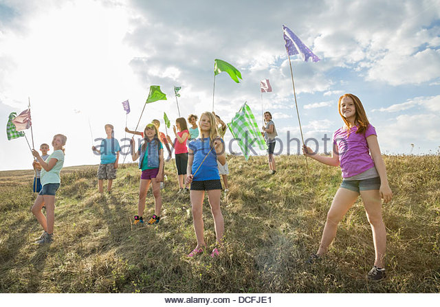 Group of kids holding flags up on a hill - Stock-Bilder
