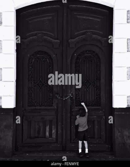 Rear View Of Boy Standing Against Arch Door - Stock-Bilder