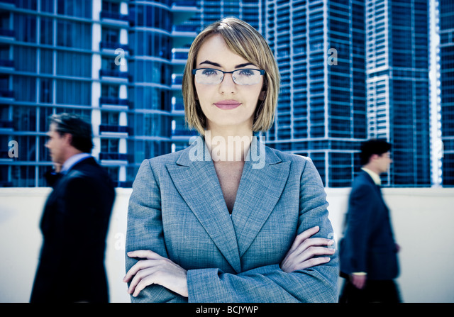 Young pretty businesswoman staring into camera with motion blurred businessmen walking by - Stock Image