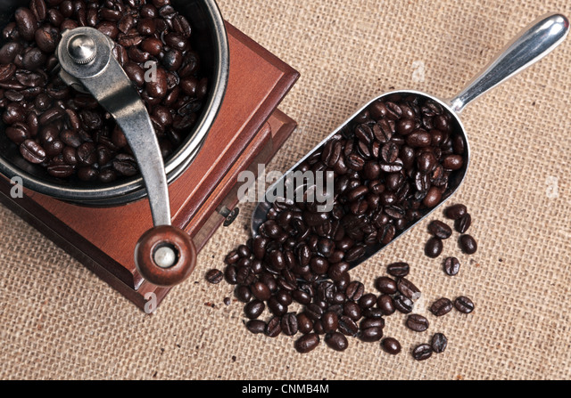 Photo of a hand operated traditional coffee grinder with a scoop full of arabica beans on a hessian background. - Stock Image