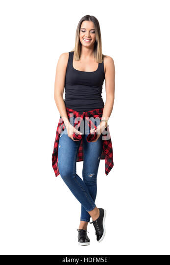 Happy young shy woman smiling and looking down wearing casual clothes. Full body length standing portrait isolated - Stock Image