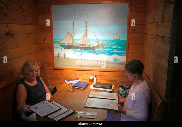 Massachusetts Cape Cod Orleans Hearth 'n Kettle Restaurant booth woman menu painting - Stock Image