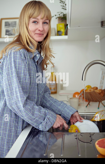 Woman In Kitchen Doing The Dishes - Stock-Bilder