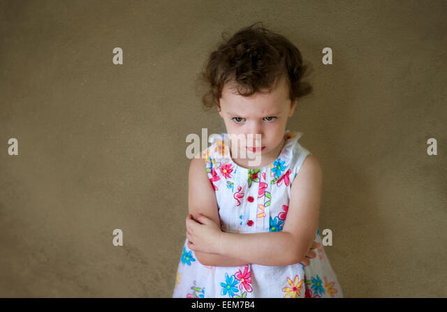 Grumpy girl (2-3) in floral patterned dress standing by wall with arms crossed - Stock Image