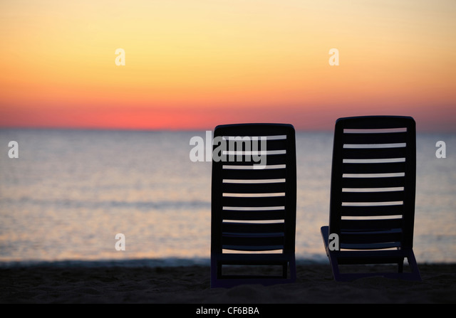 In  evening at  seaside two plastic chairs cost in  evening during sunset - Stock Image