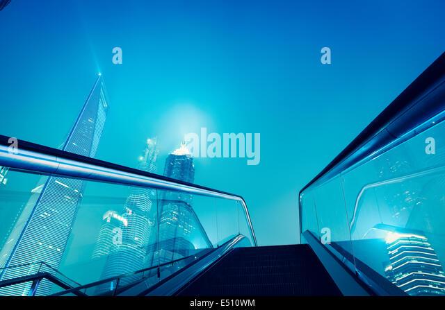 escalator and shanghai skyline at night - Stock Image