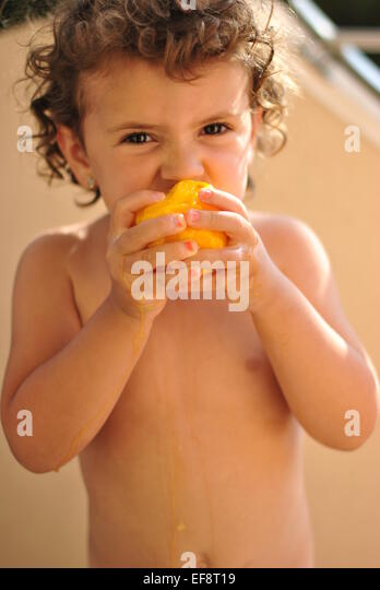 Portrait of girl (2-3) eating peach - Stock Image