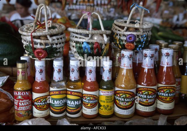 West Indies St. Lucia Castries Market spices sauces for sale bottles baskets - Stock Image