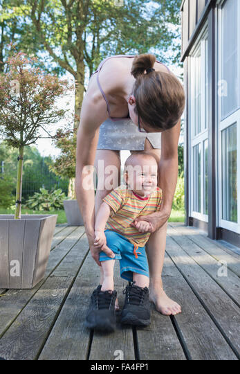 Baby boy stepping to his father shoes with mother assisting him, Munich, Bavaria, Germany - Stock Image