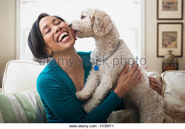 Black woman petting dog on sofa - Stock Image