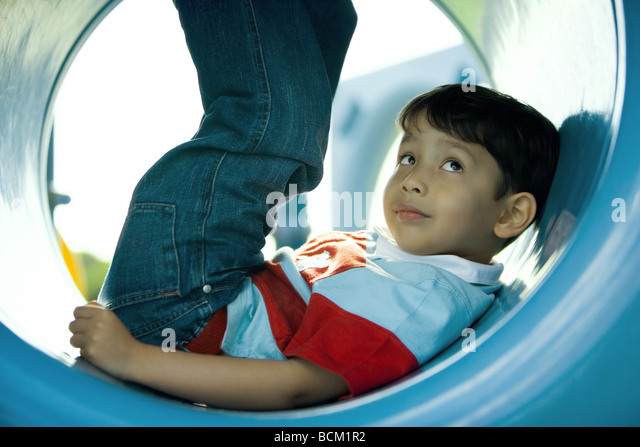Boy lying in playground tunnel with legs up, looking up, close-up - Stock Image