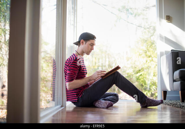 Man wearing a baseball cap backwards, sitting on the floor in a living room, looking at a digital tablet. - Stock Image
