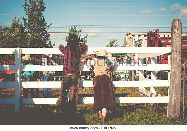USA, Connecticut, Rear view of couple at rodeo leaning on cattle fence - Stock Image