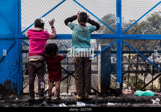 Children standing on a bridge looking through a fence at train tracks, Delhi, India - Stock Image