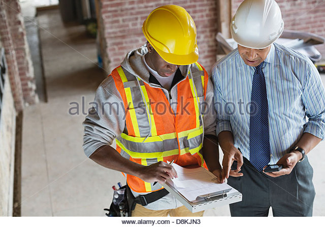 High angle view of tradesman and architect discussing work order at construction site - Stock Image