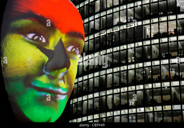 Huge sculpture of a face illuminated by an image of a Ghanaian flag painted face during the festival of lights 2011 - Stock Image