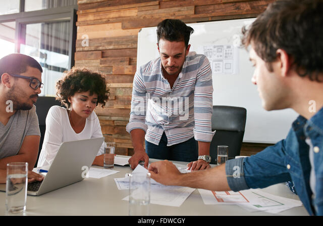 Young man discussing market research with colleagues in a meeting. Team of young professionals having a meeting - Stock Image