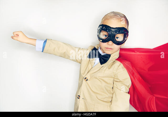 Studio shot of little boy in red cloak and aviator glasses posing with hand straight in studio. - Stock Image