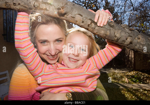A mother embracing her daughter who is hanging from a tree branch - Stock-Bilder