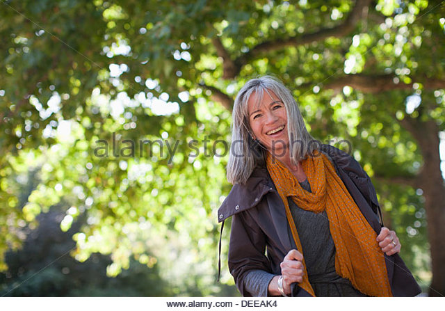 Portrait of happy woman in park - Stock Image