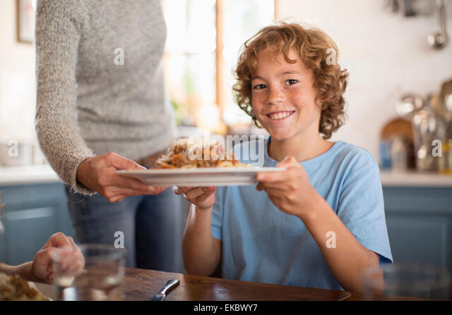 Mother serving spaghetti to children at dining table - Stock-Bilder