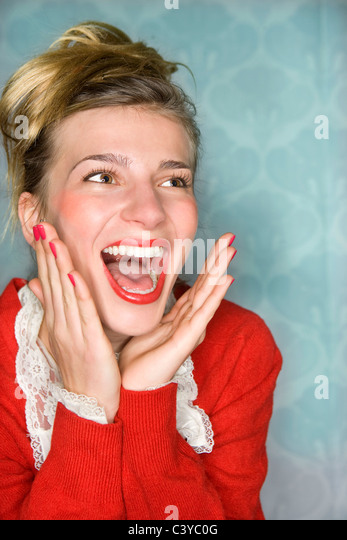 Young woman happy surprise hands up, red - Stock Image