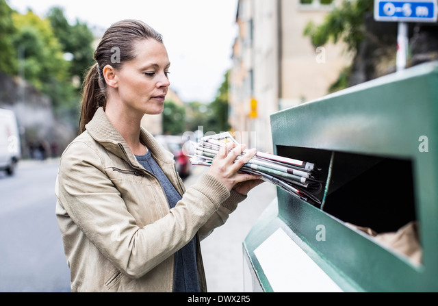 Mid adult woman putting newspapers into recycling bin - Stock-Bilder
